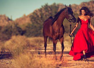 Glamorous woman walking in Arizona desert with Arabian horse