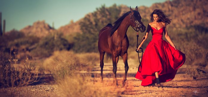 Glamorous woman walking in Arizona desert with Arabian horse
