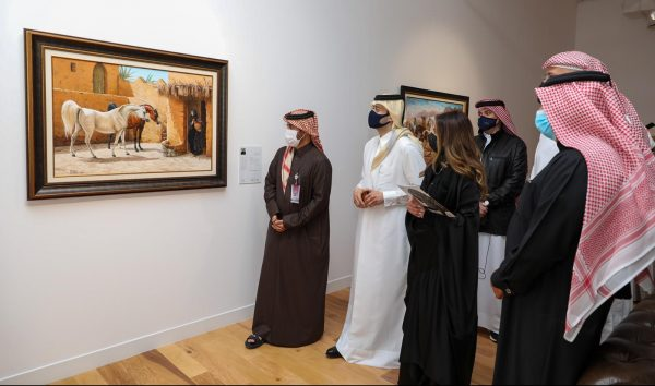 Dignitaries looking at art auction exhibits